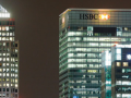 skyscraper at night with hsbc logo at the top