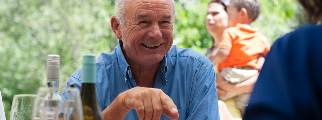 old man smiling and laughing in a garden