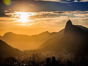Rio de Janeiro during sunset showing houses in a valley with Christ the redeemer on the right