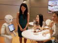 pepper, the white humanoid robot sits next to a couple at a cafe table drinking coca cola
